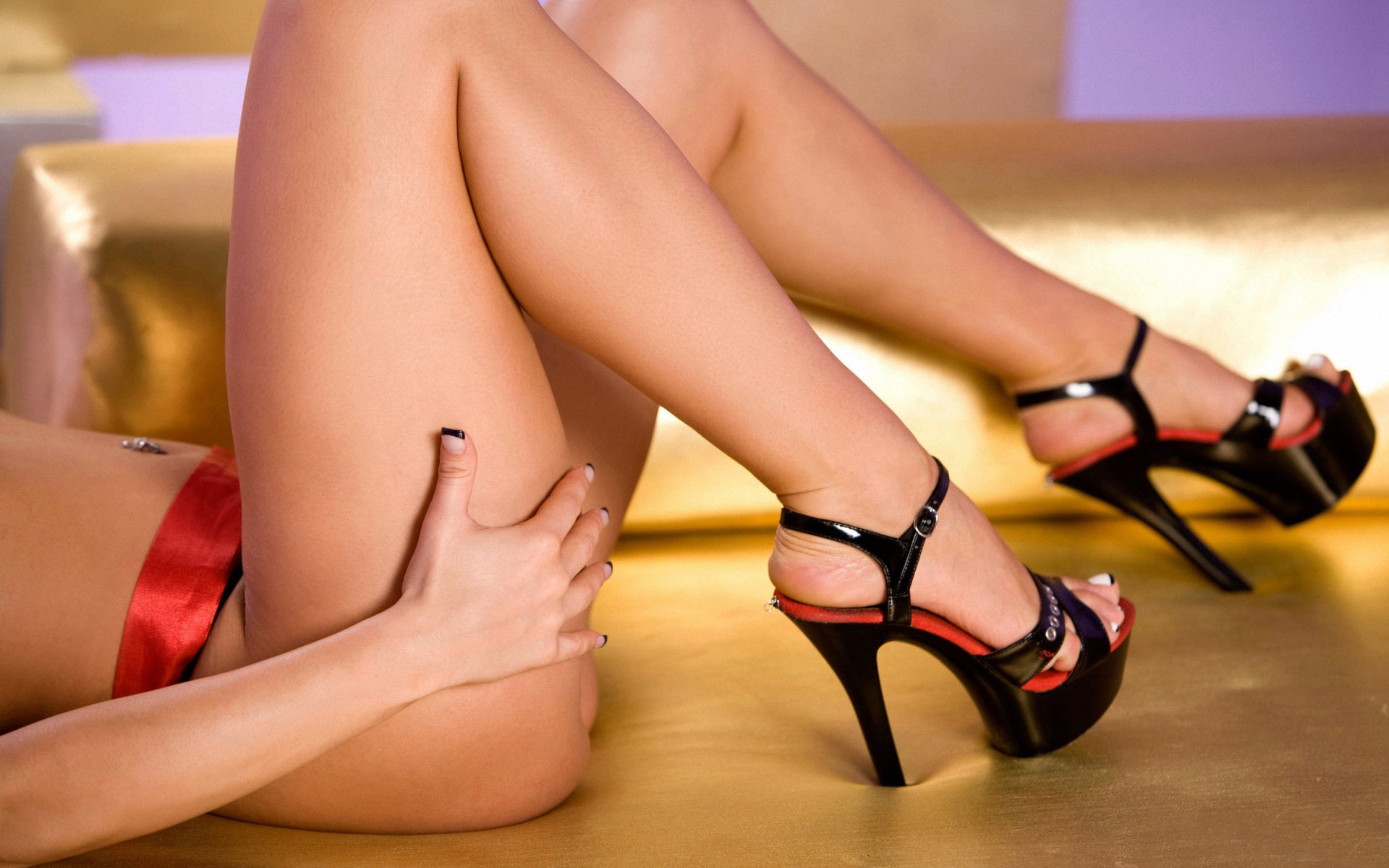 Female legs in black fishnet stockings and red shoes on high heels stock photo