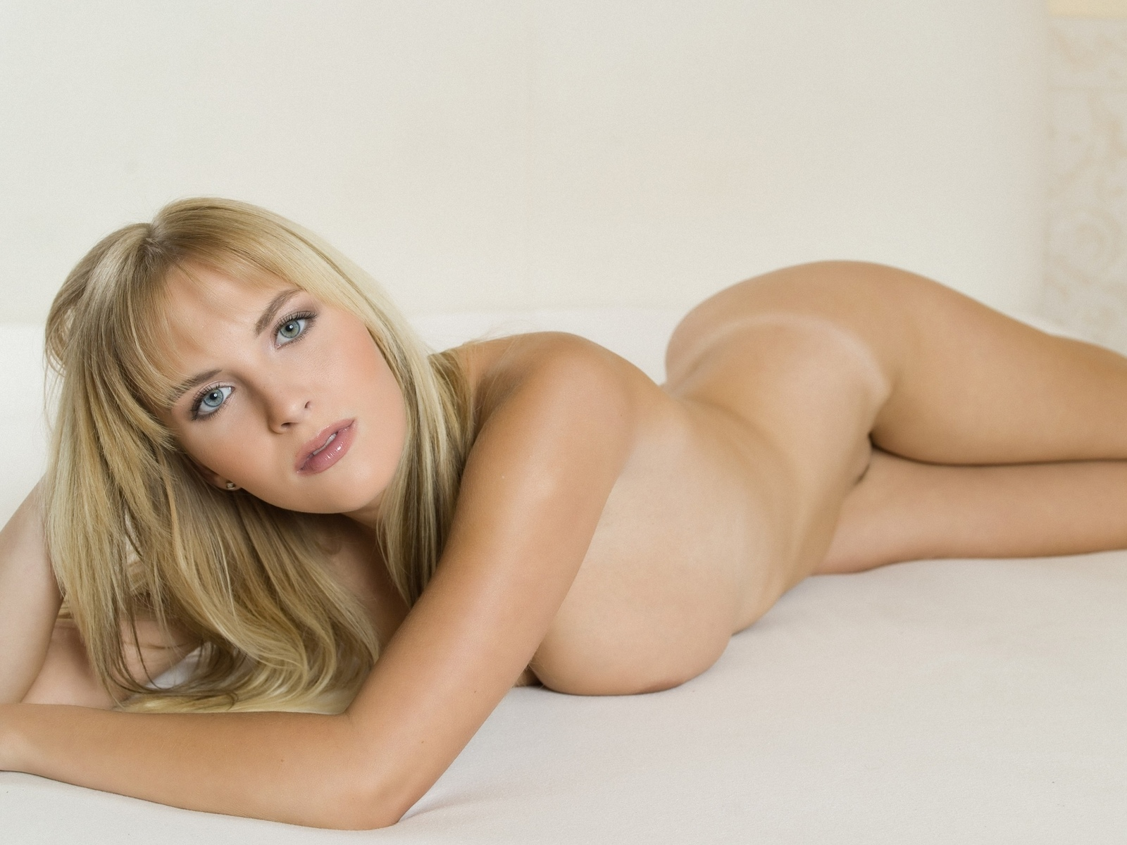 Naked blonde girl with backpack on her back