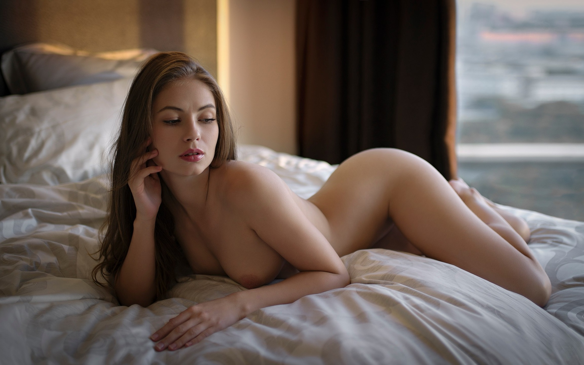 Beautiful Girl With Long Brown Hair Sitting In Bed With White Linens, Covering Her Naked Body With The Blanket, Looking