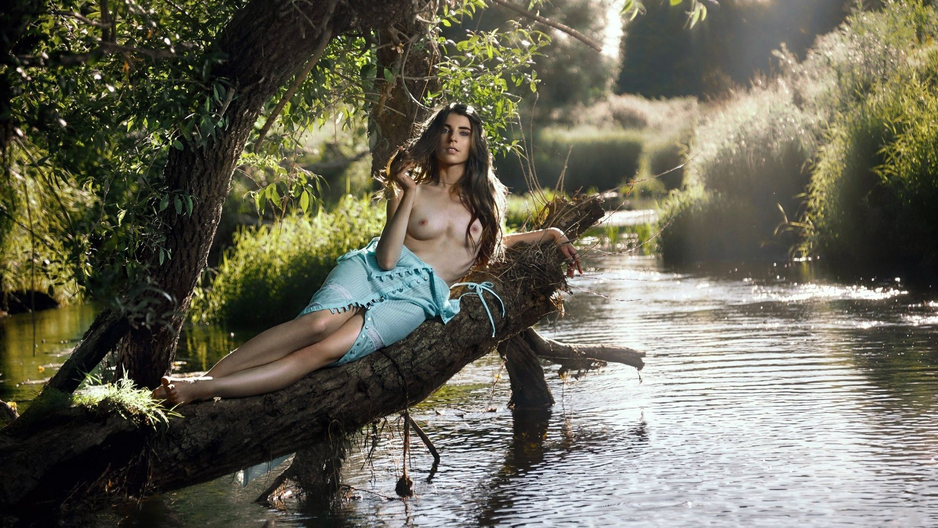 Young topless woman in a river image