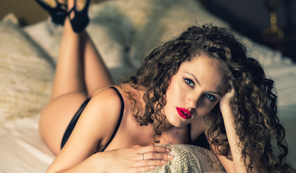 women, curly hair, blue eyes, ass, in bed, portrait, ntonio irlando, black lingerie, pillow, lying on front, high heels, feet in the air, pink nails